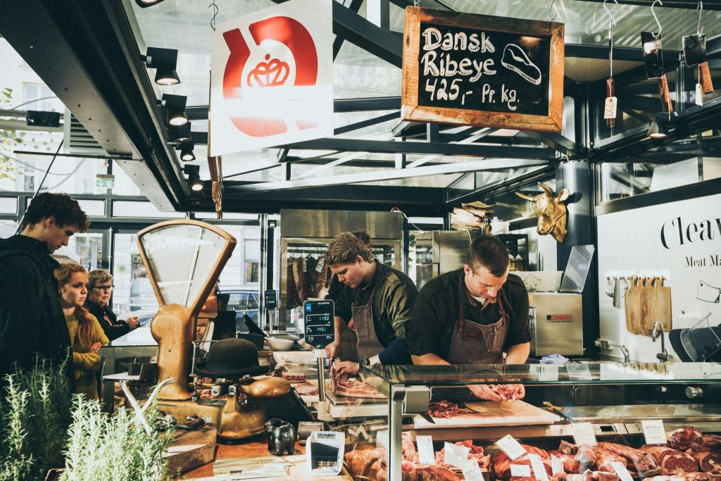 A group of butchers at a meatshop prepares an order for a customer. Photo by Nick Karvounis on Unsplash.